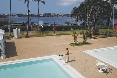 Ivory Coast. A hotel worker cleans a swimming pool in Abidjan.